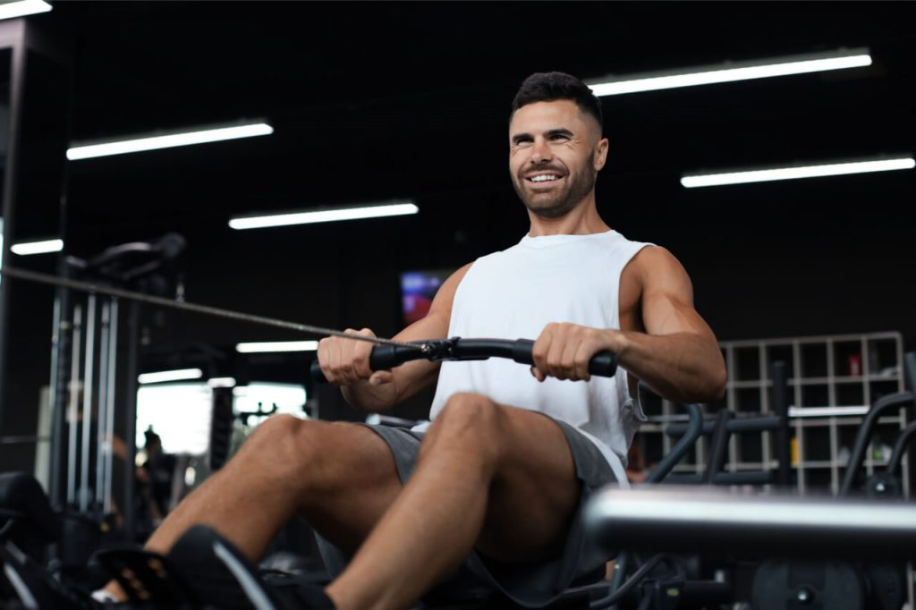 The man exercises on a fitness machine.
