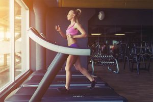 The woman has a regular exercise on the treadmill.